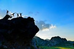 Klättrare firar på bergöverkant arkivbild