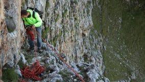 Klättrare ner från klippan på ett rep lager videofilmer