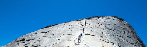 Klättrare som använder kablar för att stiga halv kupol i den Yosemite nationalparken i Kalifornien USA royaltyfri foto