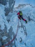 Klättrare som klättrar på is arkivfoto