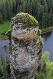 Klättrare upptill av en brant klippa ovanför floden royaltyfri foto