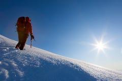 Klättraren går på en glaciär Vintersäsong, klar himmel Arkivbild