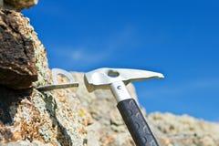 Klättraren hammers i kroken för carbine in i rock royaltyfria bilder