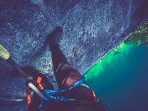 Klättraren ser ner på att klättra på en brant vägg, via ferrata royaltyfria bilder