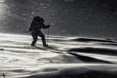 Klättraren slåss med dåligt väder i vinterbergen Arkivfoton