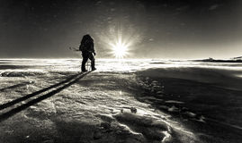 Klättraren slåss med dåligt väder i vinterbergen Arkivbild