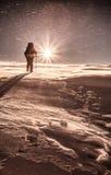 Klättraren slåss med dåligt väder i vinterbergen Arkivfoto