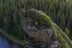 Klättraren stiger ned uppifrån av en brant klippa ovanför floden arkivfoto