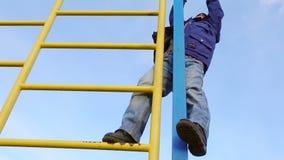 Klättring för liten unge på stege i lekplats lager videofilmer