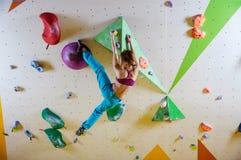 Klättring för ung kvinna i bouldering idrottshall Royaltyfri Fotografi