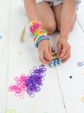Klęczeć childs wręczają robić multicoloured elastycznego zespołu bracel Zdjęcie Royalty Free