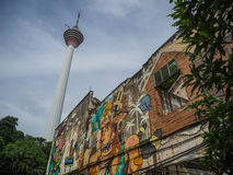 KL Tower and Graffiti. The KL Tower rises in the distance behind a graffiti covered wall in Kuala Lumpur Stock Photo