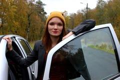 Klaar het worden Portret van jonge glimlachende dame die zich dichtbij auto en openingsdeur bevinden royalty-vrije stock afbeeldingen