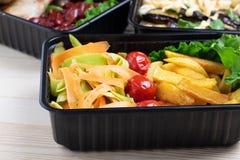 Klaar maaltijd in containers met gebraden kippenvleugels en rauwe groenten op rustieke achtergrond, kersentomaat en micro te eten stock afbeeldingen