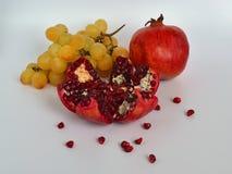 Klaar om rode rijpe sappige granaatappel met zaden en een bos van zoete gele druiven, gezond het eten concept te eten op een witt stock afbeelding
