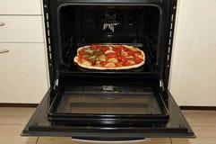 Klaar pizza in oven stock afbeelding