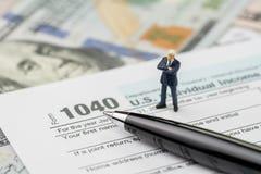 Klaar voor de periodeconcept van de belastingsvoorlegging, de miniatuur zekere zakenman die van het mensensucces zich met pen op  royalty-vrije stock afbeeldingen