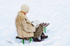 Klaar vrouw een boek in de winter stock fotografie