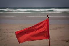 Klaff för röd flagga på stranden Fotografering för Bildbyråer