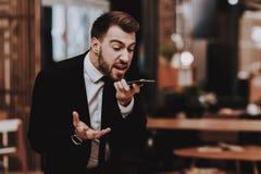 Klage eines Mannes Laut sprechen am Telefon arbeitsplatz lizenzfreie stockfotos