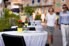 KLAGENFURF, CARINTHIA, AUSTRIA - AUGUST 07, 2018: Cafe tables on the street. In the background is a street with human silhouettes.  stock photo