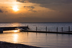 Klagshamn. Beach just after some rain and shortly before sunset, sun shining through the clouds and reflecting in the water Royalty Free Stock Image
