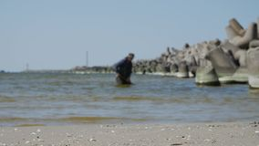 Klaipeda, Lithuania. Man searching valuable amber in sea. stock video