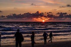 KLAIPEDA, LITUÂNIA - 19 DE AGOSTO DE 2017: Luz do por do sol com povos e sombras Por do sol na praia do mar Báltico Imagens de Stock