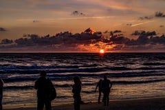 KLAIPEDA, LITUANIA - 19 DE AGOSTO DE 2017: Luz de la puesta del sol con la gente y las sombras Puesta del sol en la playa del mar Imagen de archivo libre de regalías