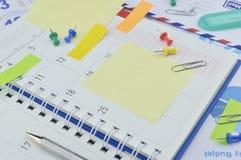 Klamerka z kolorowymi kleistymi notatkami, piórem i szpilką na biznesowym dzienniczku, Obrazy Royalty Free