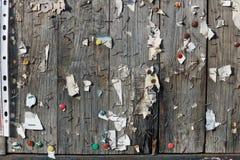 Klammern, Knöpfe, Nägel und Blätter Papier auf einem hölzernen Anschlagbrett der Straße stockfoto