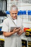 Klant die Digitale Tablet in Hardwarewinkel gebruiken Stock Afbeelding