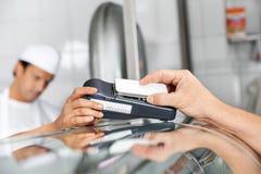 Klant die door Smartphone in Slachterij betalen stock foto
