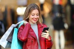 Klant die een slimme telefoon in een handelscentrum met behulp van stock foto