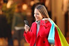 Klant die en een slimme phpone in de winter gebruiken winkelen Royalty-vrije Stock Foto