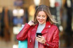 Klant die en een slimme telefoon in een wandelgalerij met behulp van winkelen Royalty-vrije Stock Foto