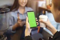 Klant die haar smartphone en nfs geavanceerd technisch gebruiken om een barista voor haar aankoop met telefoon bij een koffie te  stock foto