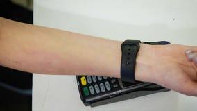 Klant die met NFC-technologie door slim horloge zonder contact op terminal in moderne koffie betalen stock footage