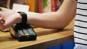 Klant die met NFC-technologie door slim horloge zonder contact op terminal in moderne koffie betalen stock video