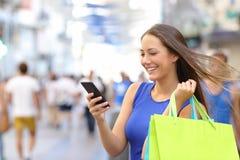 Klant die met smartphone in de straat winkelen