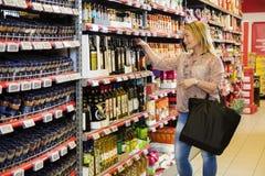 Klant die Olive Oil In Supermarket kiezen Stock Foto's