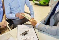 Klanten die geld geven aan autohandelaar in autosalon Royalty-vrije Stock Foto