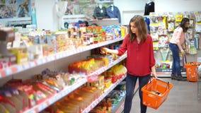Klanten die producten in supermarkt kiezen stock video