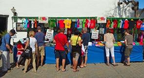 Klanten die T-shirt bij de marktkraam bekijken Stock Fotografie