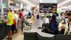 Klanten die voor het winkelen bij een supermarkt betalen Lijn bij het contante geld stock video