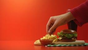 Klantenhand die heerlijke frieten met saus, rijk aan calorieënmaaltijd nemen stock video