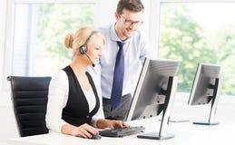 Klantenondersteuningsexploitanten in formalwear werkende gebruikende computers Stock Foto