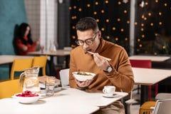 Klantenzitting in restaurant en het leren om een schotel met Chinese eetstokjes te eten stock afbeelding