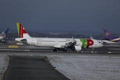 KLAPPAir Portugal nivå som åker taxi på landningsbana i den Munich flygplatsen, Tyskland, vintertid med snö royaltyfria bilder