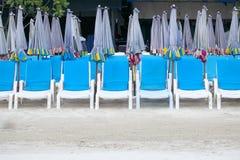 Klappstühle und Regenschirme auf dem Strand Stockfoto